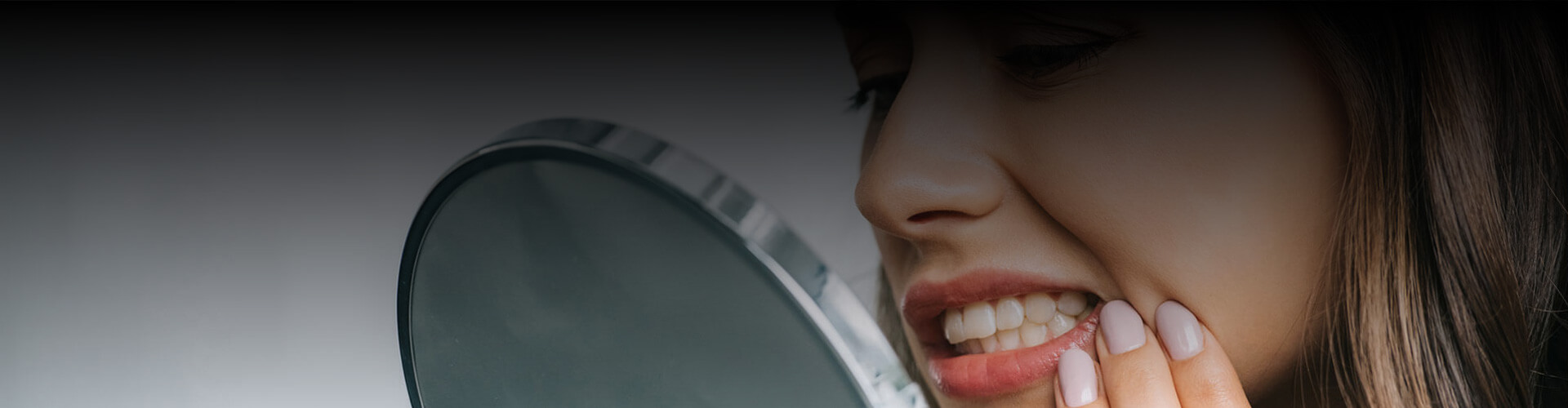 Cropped view of woman suffering from pain looking at her teeth in mirror